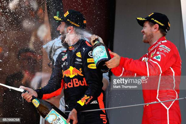 Second placed finisher Sebastian Vettel of Germany and Ferrari and third placed finisher Daniel Ricciardo of Australia and Red Bull Racing celebrates...