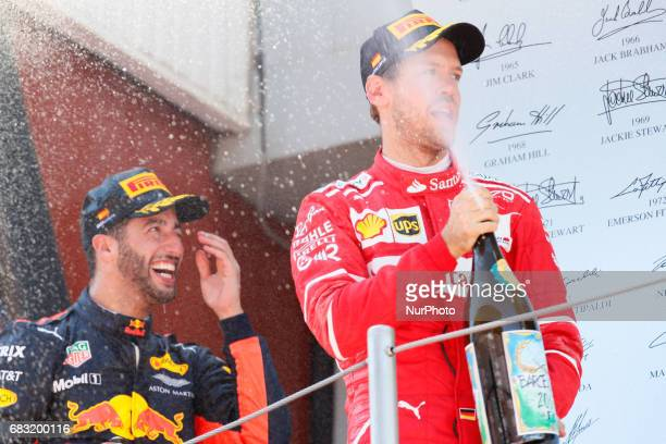 Second placed finisher Sebastian Vettel of Germany and Ferrari and third placed finisher Daniel Ricciardo of Australia and Red Bull Racing celebrate...