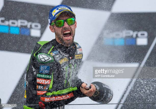 Second placed German Yamaha rider Jonas Folger sprays with champagne on the podium after the MotoGP competition of the Moto Grand Prix of Germany at...