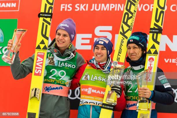 Second placed Germany's Andreas Wellinger winner Austria's Stefan Kraft and third placed Japan's Noriaki Kasai pose on the podium after the FIS World...