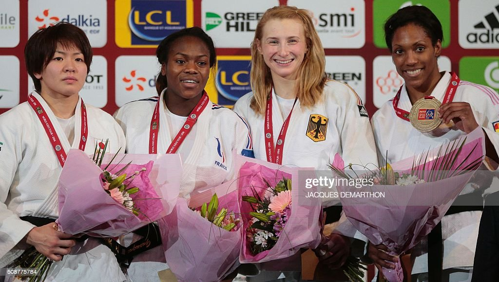 Second placed Japan's Tashiro Miku, first placed France's Clarisse Agbegnenou, and bronze medalists Germany's and Anicka Van Emden of the Netherlands pose with their medals after the women's under 63 kg final of the Paris Grand Slam Judo tournament on February 6, 2016 in Paris. / AFP / JACQUES DEMARTHON