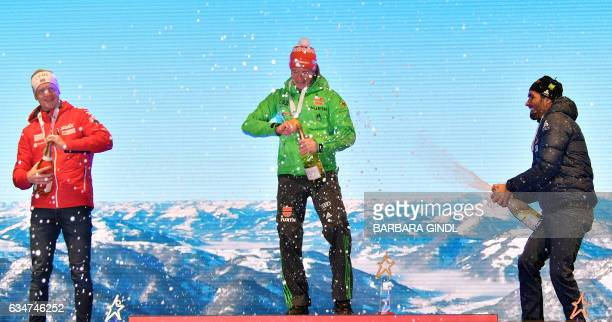 Second placed Johannes Thingnes Boe of Norway first placed Benedikt Doll of Germany third placed Martin Fourcade of France celebrate at the ceremony...