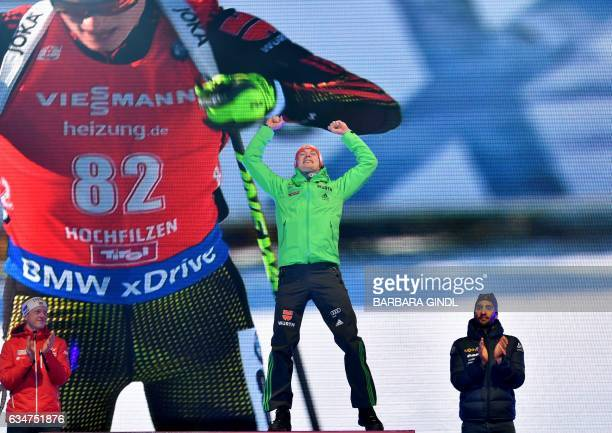 Second placed Johannes Thingnes Boe of Norway first placed Benedikt Doll of Germany third placed Martin Fourcade of France attend a ceremony after...