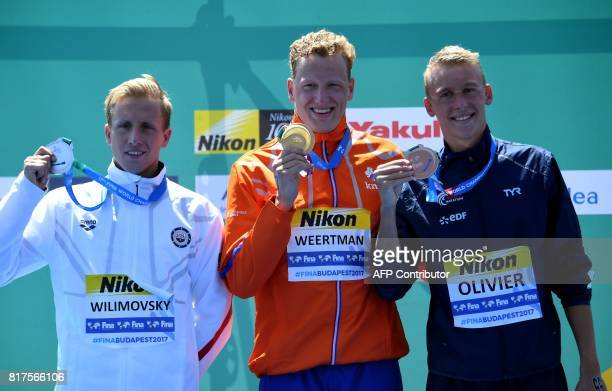 Second placed Jordan Wilimovsky of the US winner Ferry Weertman of The Netherlands and third placed MarcAntoine Olivier of France pose on the podium...