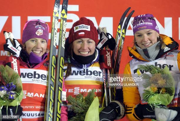 Second placed Kikkan Randall of USA winner Justyna Kowalczyk of Poland and third placed Denise Herrmann of Germany celebrating on the podium after...