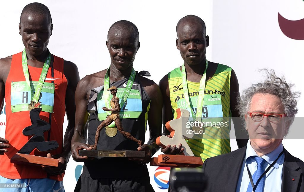 Second placed Maina Gilbert Kipkemboi, first placed Kenyan athletes Bellor Miningwo Yator and third placed Kiprono Boaz pose beside President of the French Federation of Athletics (FFA) Bernard Amsalem (front R) on the podium after winning the male category of the first ever Dakar International Marathon long 42,195km in 2h 16mm 37s according to official results in Dakar on February 14, 2016. The competition organised by the BTP Eiffage society started on February 13 in front of International Conference Center Abou Diouf (Cicad) on the outskirts of Dakar with different runs of 10 km and will end the day after, February 14, with a marathon. The BTP Eiffage society hosted the event to celebrates its 90 years of presence in Senegal. / AFP / SEYLLOU