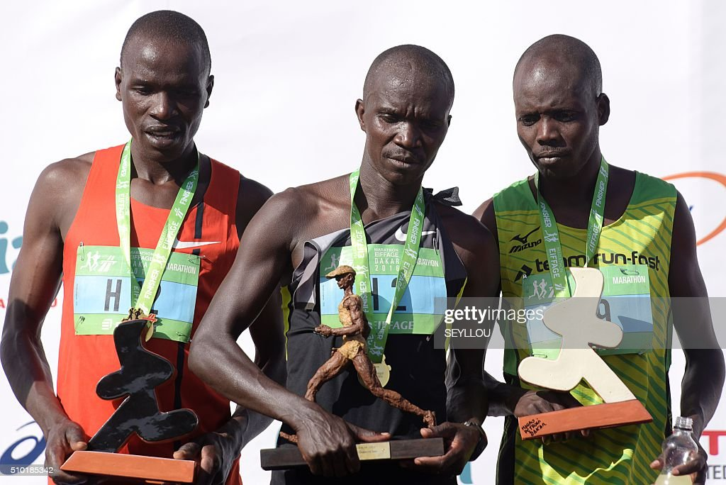 Second placed Maina Gilbert Kipkemboi,first placed Kenyan athletes Bellor Miningwo Yator and third placed Kiprono Boaz pose on the podium after winning the male category of the first ever Dakar International Marathon long 42,195km in 2h 16mm 37s according to official results in Dakar on February 14, 2016. The competition organised by the BTP Eiffage society started on February 13 in front of International Conference Center Abou Diouf (Cicad) on the outskirts of Dakar with different runs of 10 km and will end the day after, February 14, with a marathon. The BTP Eiffage society hosted the event to celebrates its 90 years of presence in Senegal. / AFP / SEYLLOU