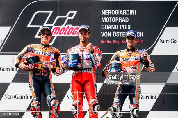 Second placed Marc Marquez of Spain winner Andrea Dovizioso of Italy and third placed Dani Pedrosa of Spain pose for photos on podium after the the...