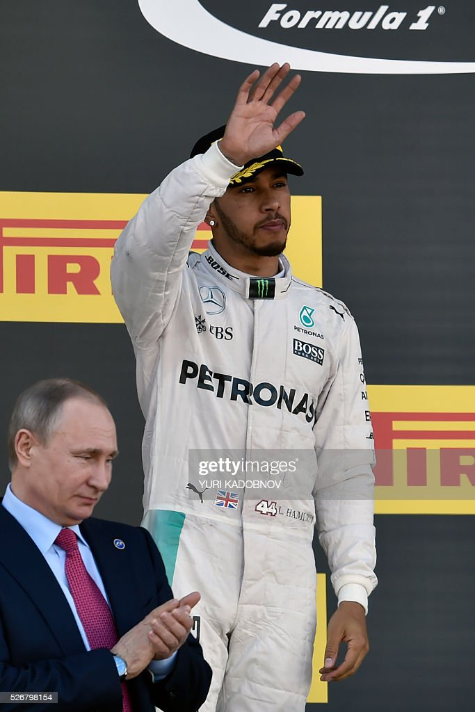 Second placed Mercedes AMG Petronas F1 Team's British driver Lewis Hamilton celebrates on the podium as Russian President Vladimir Putin stands nearby after the Formula One Russian Grand Prix at the Sochi Autodrom circuit on May 1, 2016. / AFP / YURI