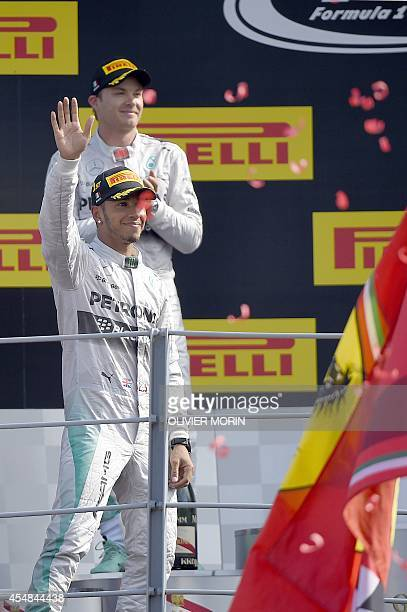 Second placed Mercedes' German driver Nico Rosberg applauds as winner Mercedes' British driver Lewis Hamilton arrives on the podium after the Italian...