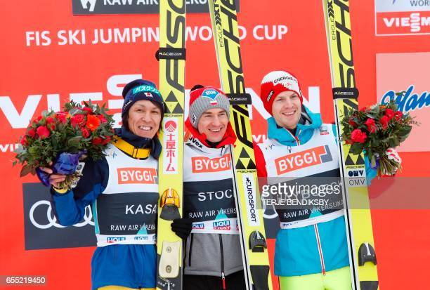 Second placed Noriaki Kasai from Japan winner Kamil Stoch from Poland and third placed Michael Hayböck from Austria pose on the podium after FIS Ski...