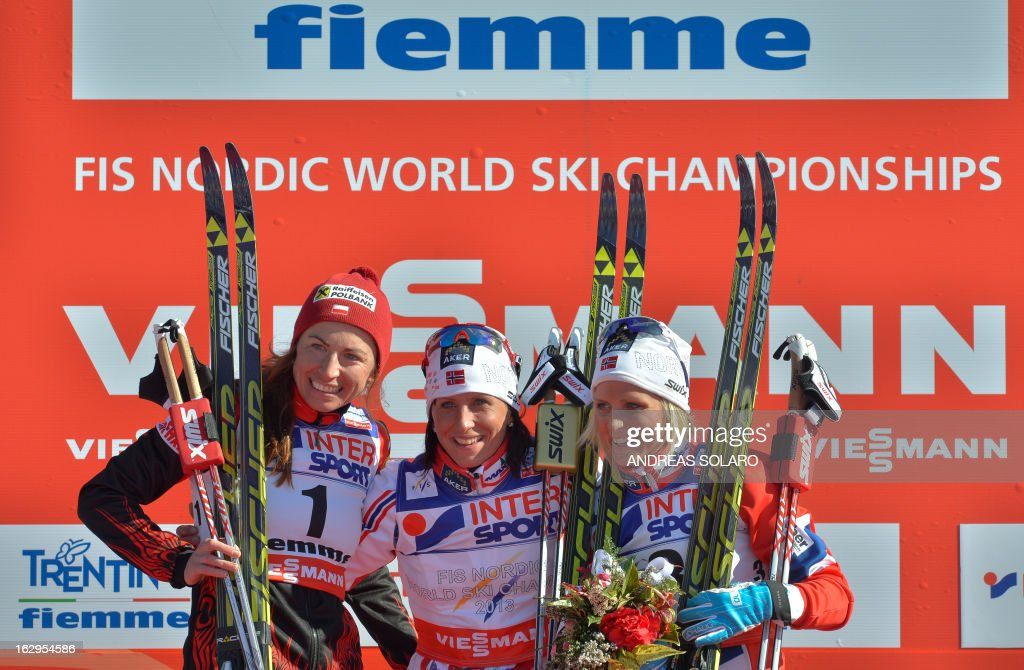Second placed Polish Justyna Kowalczyk, first placed Norway's Marit Bjoergen and third placed Norway's Therese Johaug celebrate on March 2, 2013 on the podium at the end of the Women's Cross Country 30 km Classic race of the FIS Nordic World Ski Championships at Val Di Fiemme Cross Country stadium in Cavalese, northern Italy. AFP PHOTO / ANDREAS SOLARO