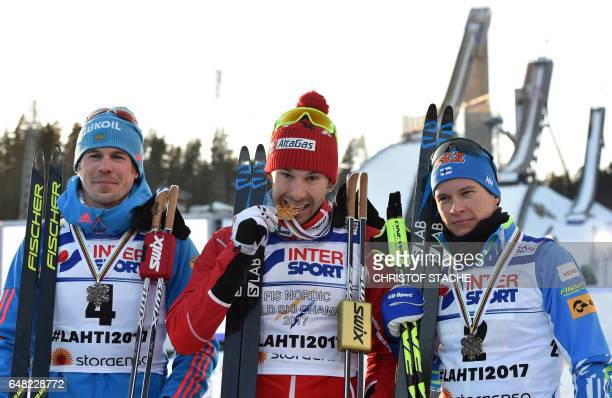 Second placed Russia's Sergey Ustiugov winner Canada's Alex Harvey and third placed Finland's Matti Heikkinen pose with the medals after the men's...