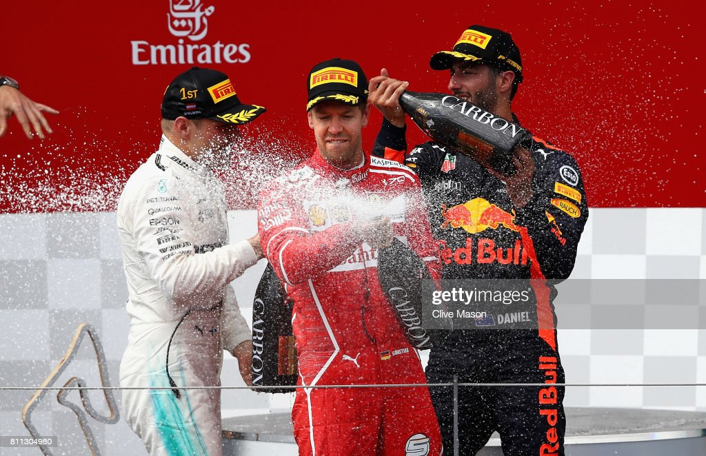 Second placed Sebastian Vettel of Germany and Ferrari celebrates on the podium in front of race winner Valtteri Bottas of Finland and Mercedes GP and third placed Daniel Ricciardo of Australia and Red Bull Racing during the Formula One Grand Prix of Austria at Red Bull Ring on July 9, 2017 in Spielberg, Austria.