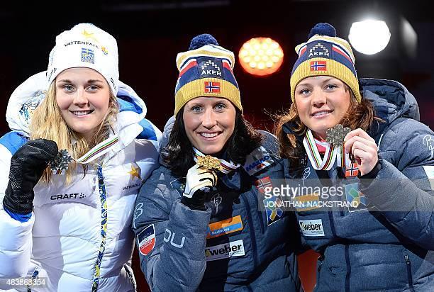 Second placed Sweden's Stina Nilsson winner Norway's Marit Bjoergen and third placed Norway's Maiken Caspersen Fallen pose on the podium during a...