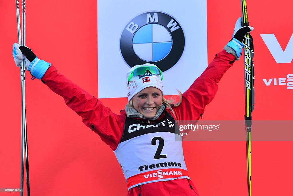 Second placed Therese Johaug of Norway celebrates on the podium of the women's 9km free final climb pursuit of the Tour de Ski in Val di Fiemme on January 6, 2013. Justyna Kowalczyk of Poland won the race ahead Therese Johaug of Norway and Kristin Stoermer Steira of Norway. AFP PHOTO / GIUSEPPE CACACE