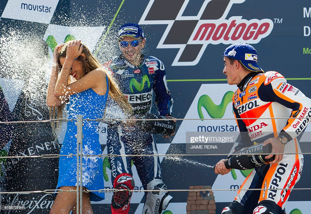 Second placed Yamaha Team's Spanish rider Jorge Lorenzo (C) and race winner Repsol Honda's Spanish rider Marc Marquez (R) celebrate on the podium after the Moto GP race of the Aragon Grand Prix at the Motorland racetrack in Alcaniz on September 25, 2016. / AFP / JAIME