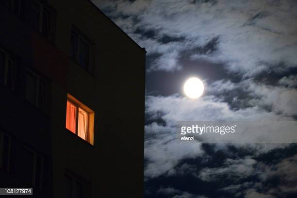 Second Story House Window Lit Against Night Sky