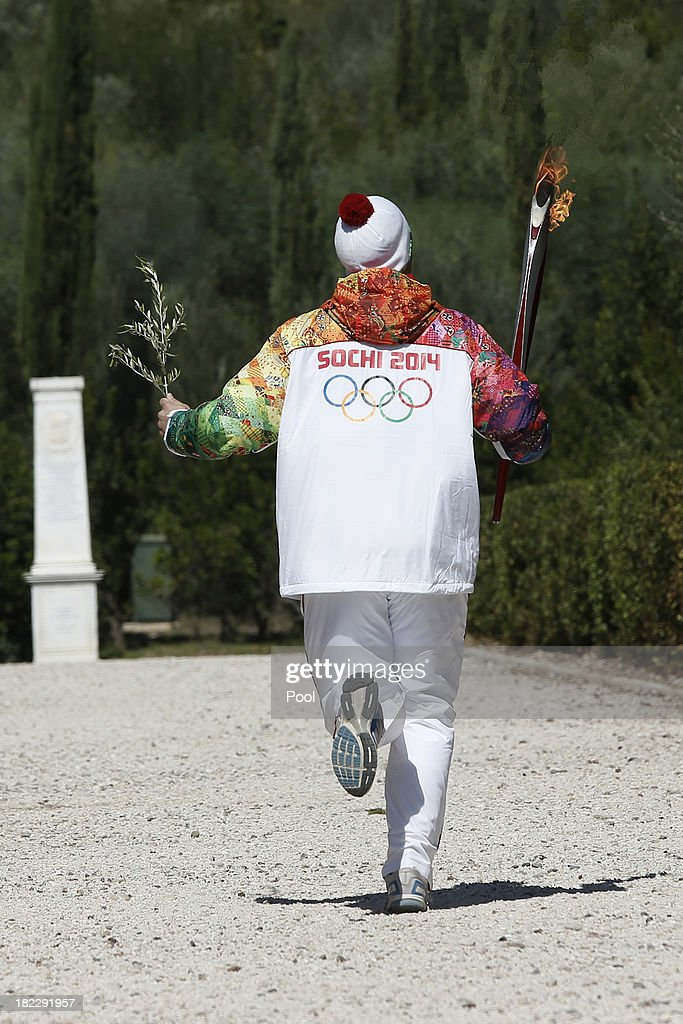 Second torchbearer Alexander Ovechkin of Russia leaves the Pierre de Coubertin monument during the torch relay September 29, 2013 in Olympia, Greece. After the lighting ceremony of the Olympic flame at Ancient Olympia, in west southern Greece, the torch will the be relayed to the Russian resort of Sochi, which will host the Winter Olympics on February, 2014