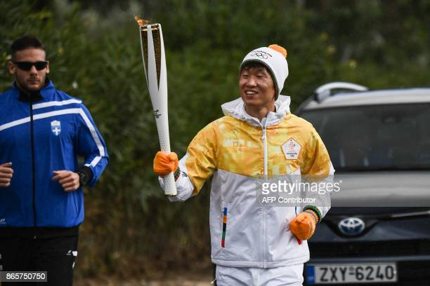 Second torchbearer for Pyeongchang 2018 former South Korean international footballer Park JiSung holds the Olympic torch at the Temple of Hera on...