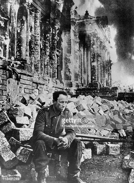 Second World War German soldier sits amongst the ruins of the Reichstag in Berlin after the Russian army entered the city in 1945