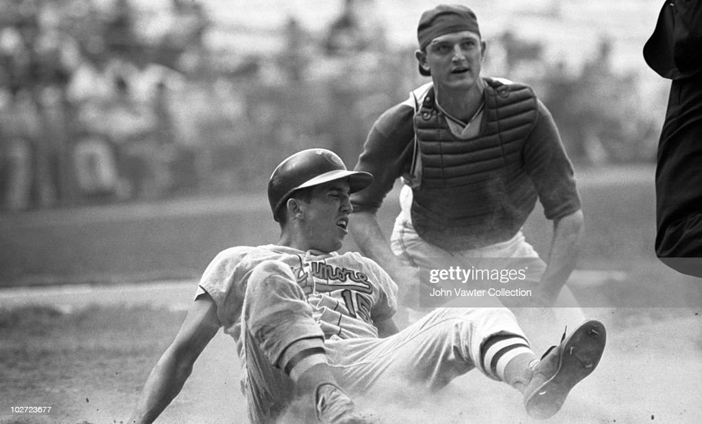 Secondbaseman Davey Johnson of the Baltimore Orioles slides home safely as catcher Phil Roof of the Kansas City A's applies the tag too late during...