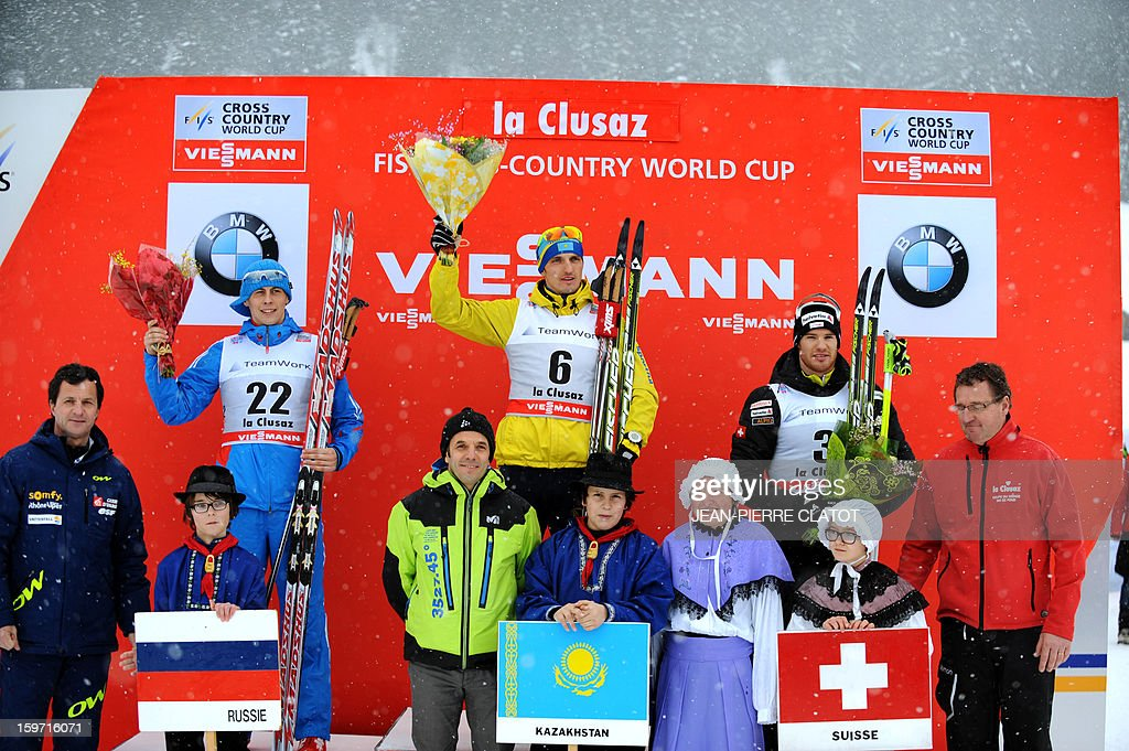 Second-place winner Alexander Bessmertnykh of Russia, first-place winner Alexey Poltoranin of Kazakhstan, and third-place winner Dario Cologna of Switzerland celebrate during the podium ceremony at the end of the men's World Cup Nordic skiing cross country 15km Mass Start race, on January 19, 2013, in La Clusaz,southern France. AFP PHOTO / Jean Pierre Clatot