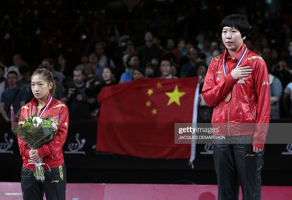 Second-placed China's Liu Shiwen (L) and winner China's Li Xiaoxia (R) listen their national anthem, on May 19, 2013 in Paris, during the trophy ceremony of the Women's Singles of the World Table Tennis Championships.