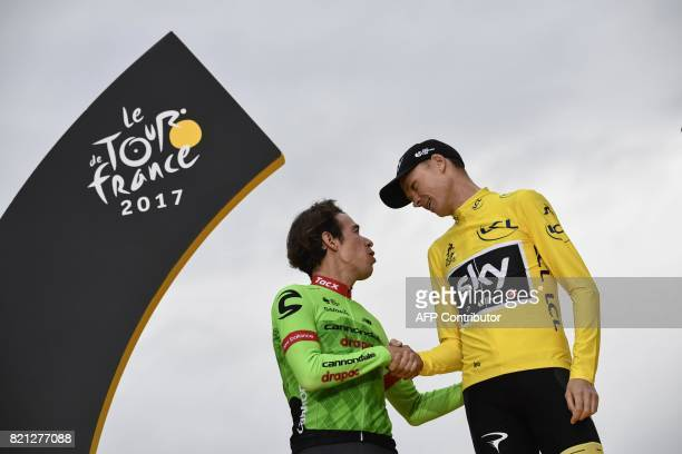 Secondplaced Colombia's Rigoberto Uran speaks with Tour de France 2017's winner Great Britain's Christopher Froome wearing the overall leader's...