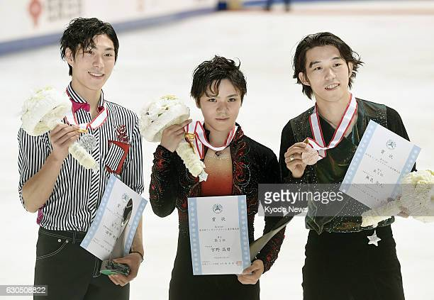 Secondplaced Keiji Tanaka winner Shoma Uno and thirdplaced Takahito Mura pose for photos after the men's figure skating event at the national...