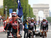 Secondplaced overall Australia's Cadel Evans carries the Australian flag as he rides with his teammates during an honor lap at the end of the 94th...