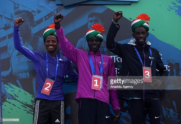 Secondplaced runner Seboka Dibaba winner Gideon Kipketer and thirdplaced Marius Kimutai hold their medals after the 2016 Mumbai Marathon in Mumbai on...