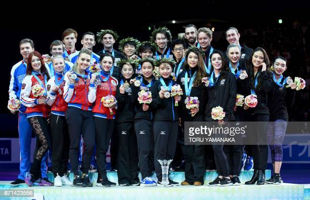 Secondplaced Russian skaters firstplaced Japan's skaters and thirdplaced US skaters pose for photographers during the awards ceremony at the World...