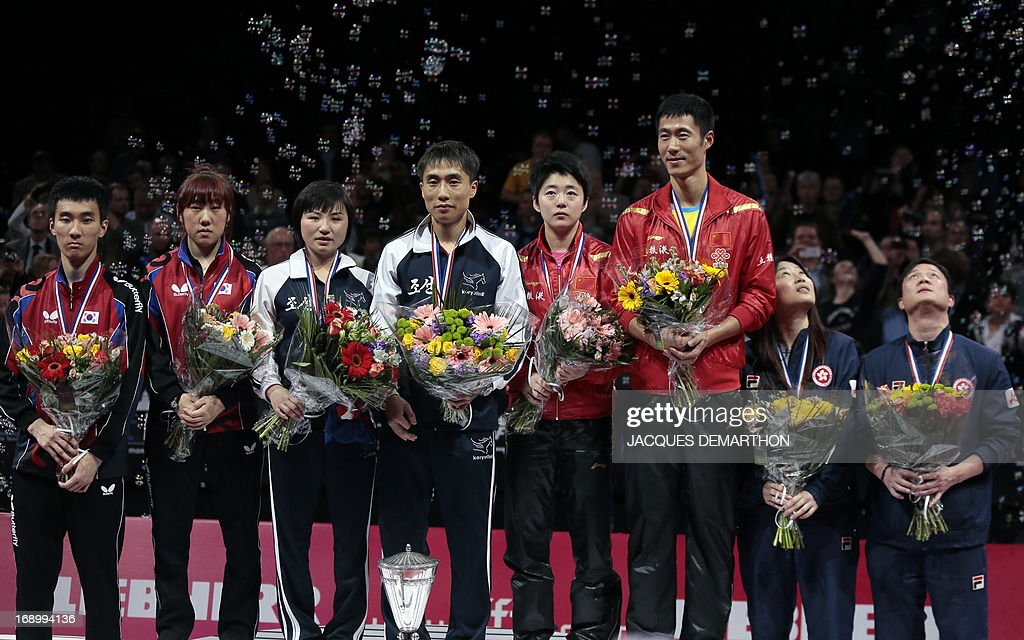 Second-placed South Korea's Lee Sangsu (L) and Park Youngsook (2nd L), Winner North Korea's Kim Jong (3rd L) and Kim Hyok Bong (4th L), and third-placed China's Rao Jingwen (4th R) and Wang Liqin (3rd R), and third-placed Hong Kong's Jiang Huajun (2nd R) and Cheung Yuk (R) stand on the podium of the mixed doubles category of the World Table Tennis Championships on May 18, 2013 in Paris. North Korea won the title. AFP PHOTO / Jacques DEMARTHON