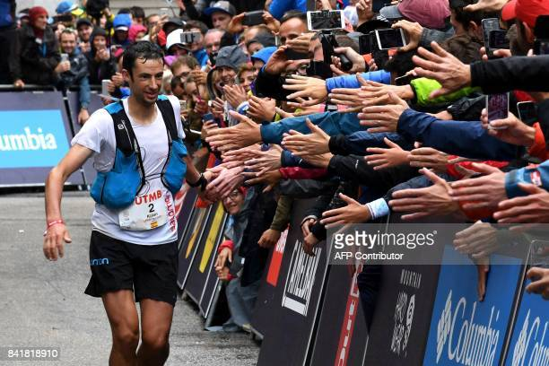 Secondplaced Spanish athlete and former Mount Blanc Ultra Trail winner Kilian Jornet greets supporters as he runs towards the finish line of the 15th...