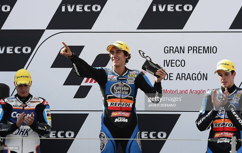 Second-placed Team Calvo's Spanish rider Maverick Vinales (L) and third-placed Estrella Galicia 0,0's Spanish rider Alex Marquez (C) applaud winner Estrella Galicia 0,0's Spanish rider Alex Rins on the podium of the Moto 3 race of the Aragon Grand Prix at the Motorland racetrack in Alcaniz on September 29, 2013. AFP PHOTO / JAVIER SORIANO