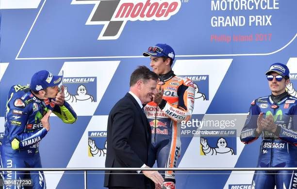 Secondplaced Yamaha rider Valentino Rossi of Italy kisses a shield as winner Honda rider Marc Marquez of Spain and thirdplaced Yamaha rider Maverick...