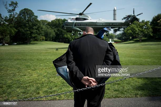 A Secret Service agent ducks rotor wash as Marine One lands to pick up US President Barack Obama on the South Lawn of the White House May 29 2013 in...