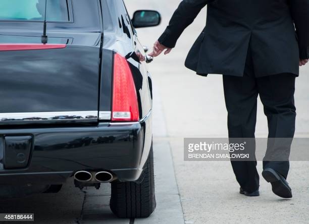 A Secret Service Agent keeps his hand on US President Barack Obama's armored limo as it departs Andrews Air Force Base October 31 2014 in Maryland...