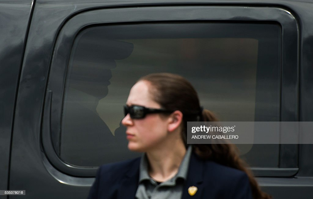 A secret service agent looks on as Republican presidential candidate Donald Trump (in car) leaves an event at the annual Rolling Thunder 'Ride for Freedom' parade ahead of Memorial Day in Washington, DC, on May 29, 2016. / AFP / Andrew CABALLERO