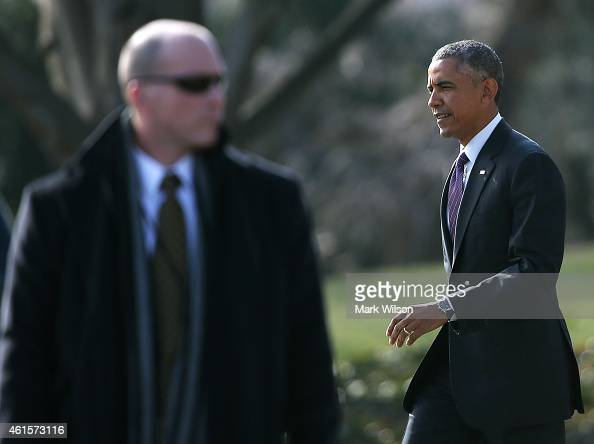 Secret Service agent stands guard as President Barack Obama walks to Marine One while departing the White House January 15 2015 in Washington DC...