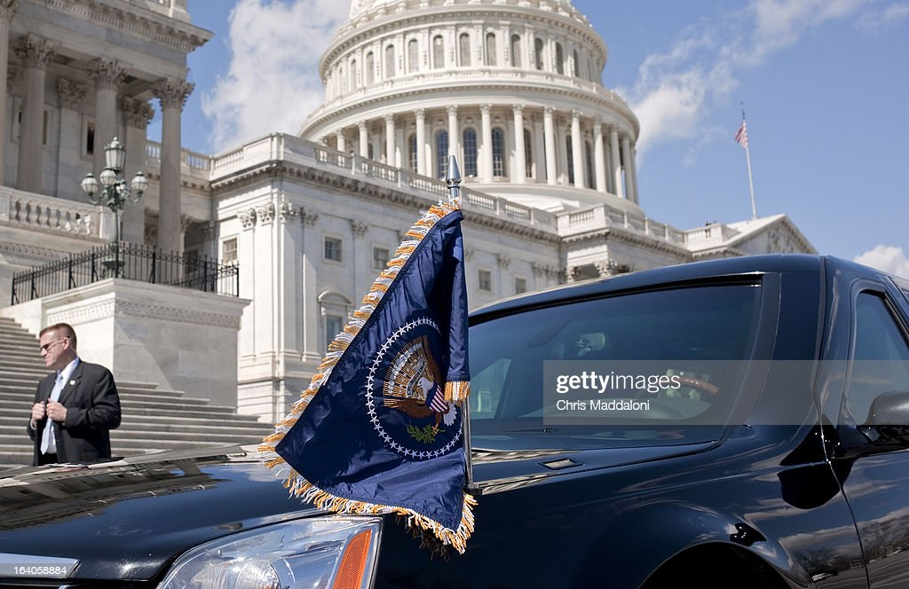 A Secret Service agent waits for President Barack Obama to enter his car to leave the Friends of Ireland luncheon at U.S. Capitol from the East Front House steps.