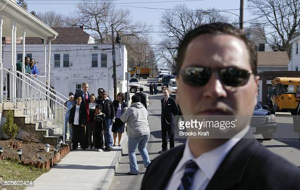 A US Secret Service agent watches as President George W Bush meets with residents as he takes a tour of new homeowners' houses before holding a...