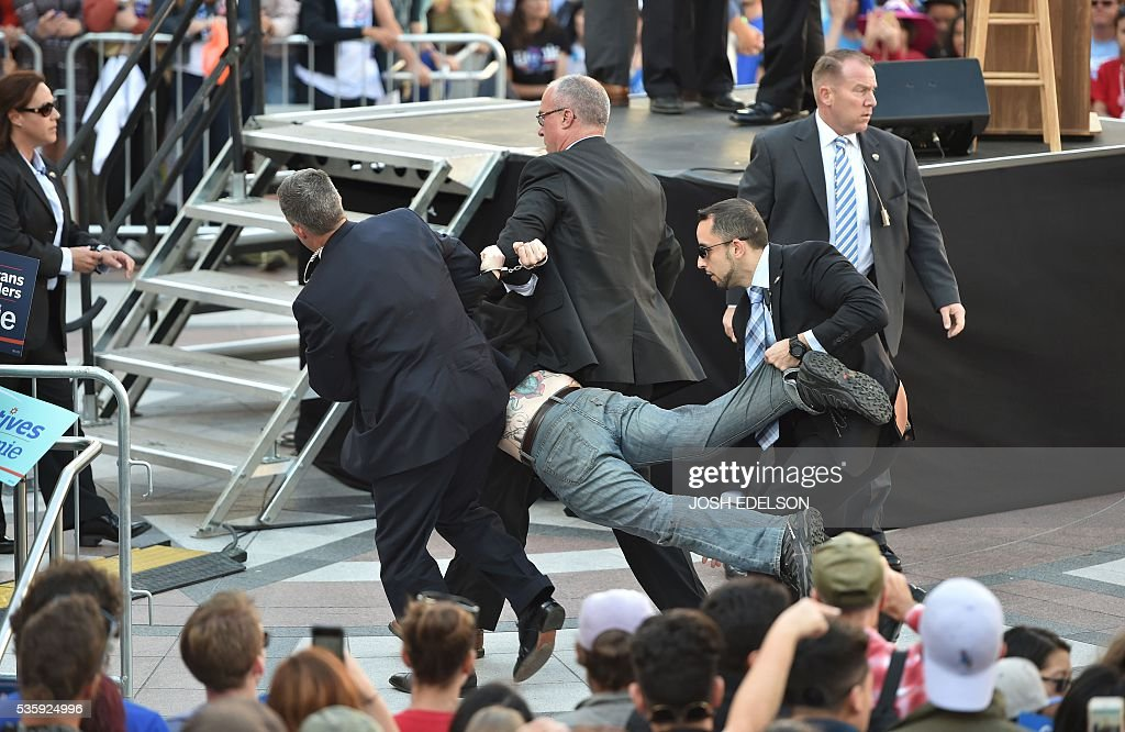Secret Service agents arrest a man for climbing over a barricade and approaching Democratic presidential candidate Bernie Sanders while he speaks at Frank Ogawa Plaza in Oakland, California on May 30, 2016. / AFP / JOSH