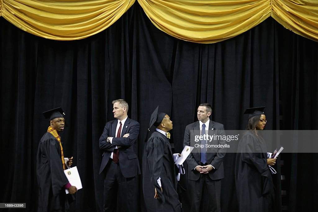 U.S. Secret Service agents keep watch as graduates of Bowie State University arrive for the school's graduation ceremony at the Comcast Center on the campus of the University of Maryland May 17, 2013 in College Park, Maryland. First lady Michelle Obama delivered the commencement speech for the 600 graduates of Maryland's oldest historically black university and one of the ten oldest in the country.