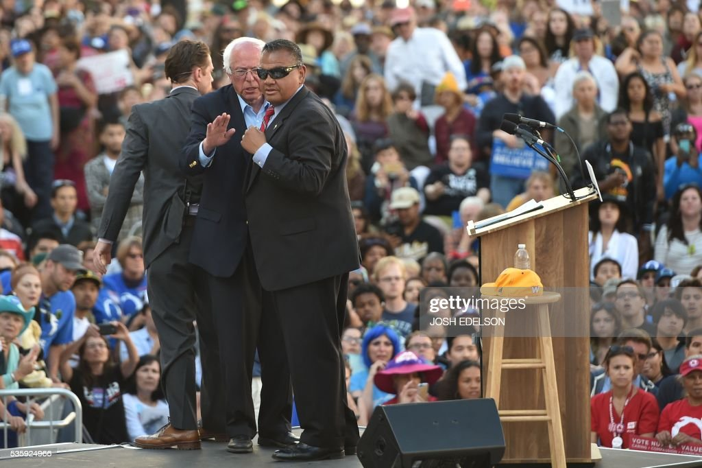 Secret Service agents protect Democratic presidential candidate Bernie Sanders (C) after multiple people climbed a barricade and approached during his speech at Frank Ogawa Plaza in Oakland, California on May 30, 2016. / AFP / JOSH