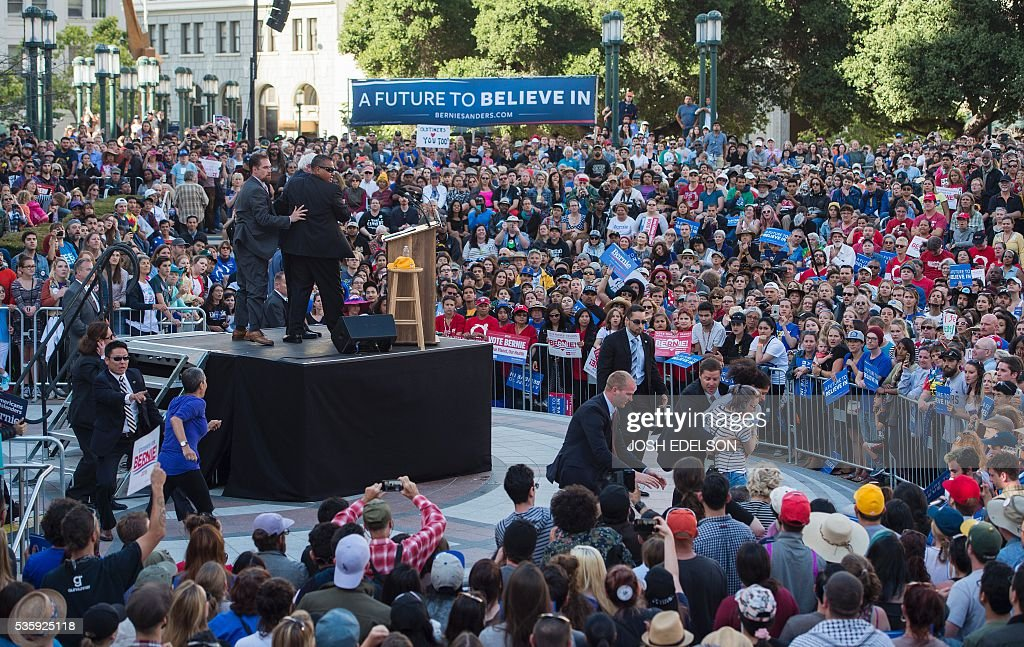 Secret service agents secure the scene after multiple people climbed a barricade and approached Democratic presidential candidate Bernie Sanders during his speech at Frank Ogawa Plaza in Oakland, California on May 30, 2016. / AFP / JOSH
