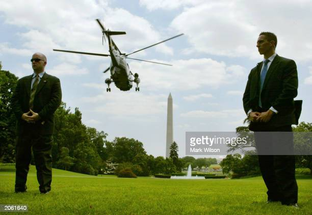 Secret Service agents stand gaurd as Marine One carrying US President George W Bush takes off from the South Lawn of the White House June 6 2003 in...