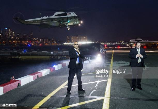 US Secret Service Agents stand guard as Marine One with US President Barack Obama board prepares to land at the Downtown Manhattan Heliport in New...