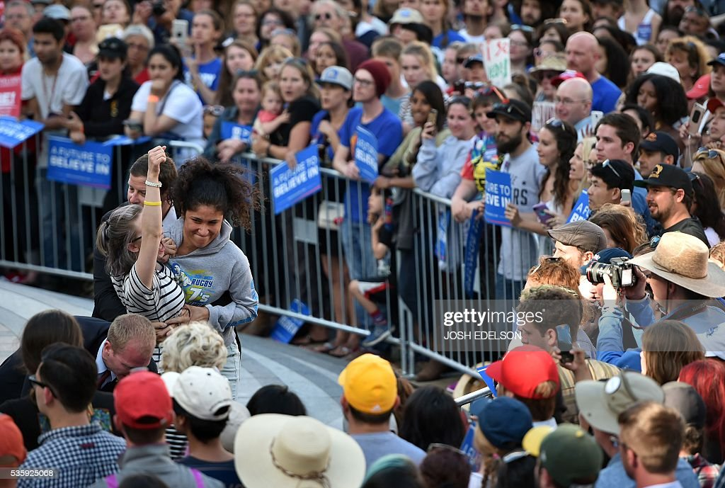Secret Service agents tackle multiple people after they climbed a barricade and approached Democratic presidential candidate Bernie Sanders during his speech at Frank Ogawa Plaza in Oakland, California on May 30, 2016. / AFP / JOSH